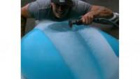 Un globo lleno de agua y una sierra a cámara lenta